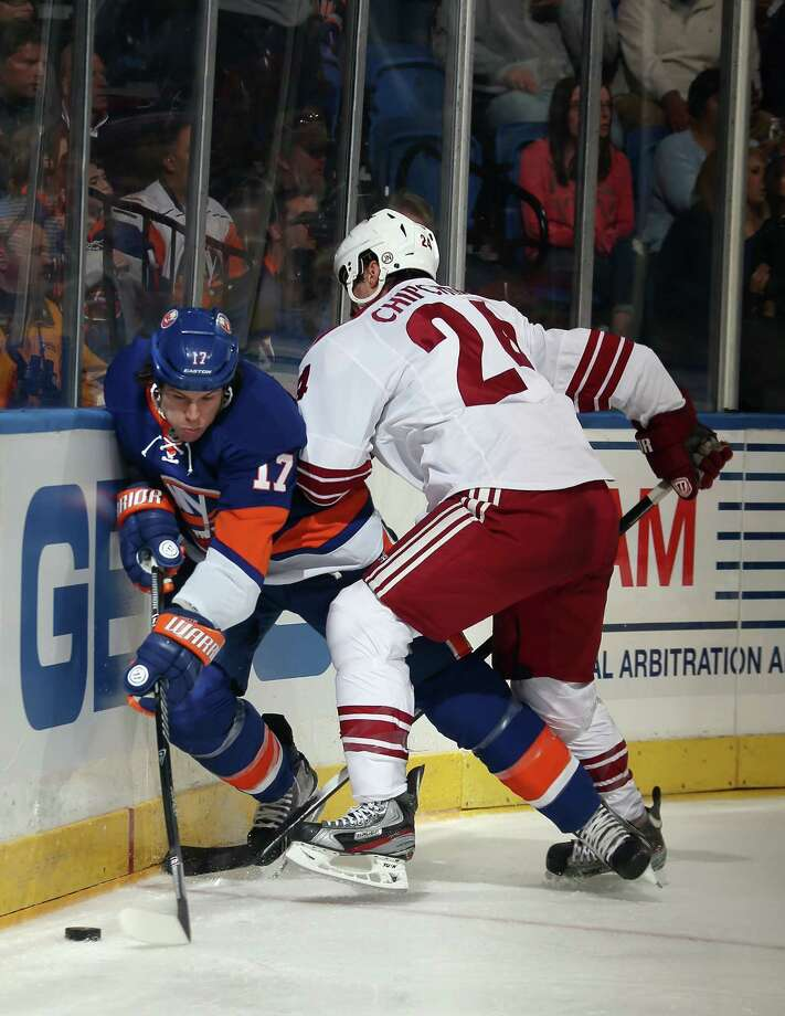 UNIONDALE, NY - OCTOBER 08: Kyle Chipchura #24 of the Phoenix Coyotes hits Matt Martin #17 of the New York Islanders into the boards at the Nassau Veterans Memorial Coliseum on October 8, 2013 in Uniondale, New York.  (Photo by Bruce Bennett/Getty Images) ORG XMIT: 181107724 Photo: Bruce Bennett / 2013 Getty Images