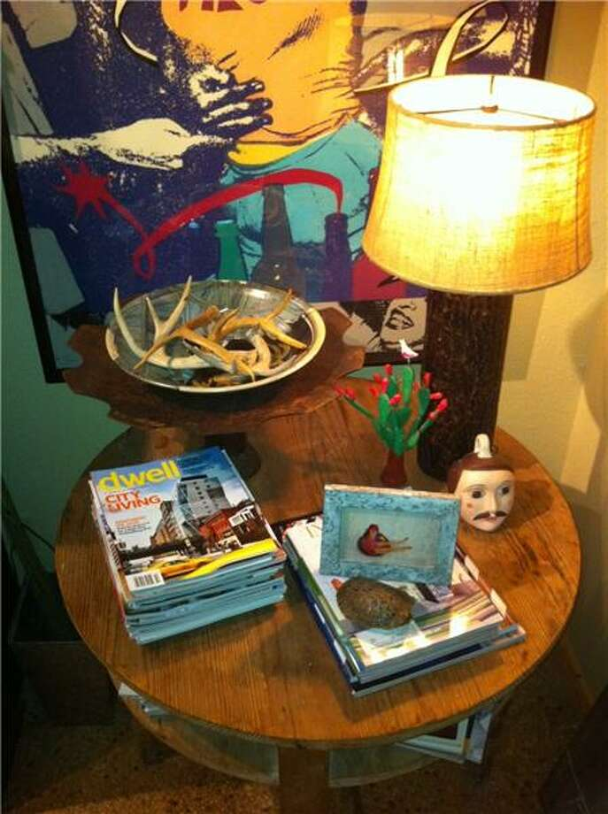 """John Bloodsworth loves this old pine table with cubby holes for stacks of magazines and books. The metal bowl on stand is made from repurposed tractor parts and farm tillers. Shed antlers fill the bowl. The lamp is a faux bois tree trunk with burlap shade. Silkscreen artwork in the background is the late Danny Geisler's """"Fiesta."""" Photo: Courtesy Photo"""