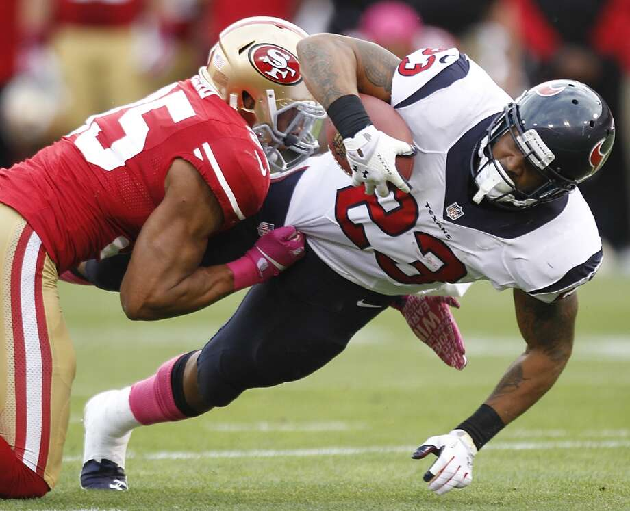 Texans running back Arian Foster is brought down by 49ers free safety Eric Reid during the first quarter. Photo: Brett Coomer, Houston Chronicle
