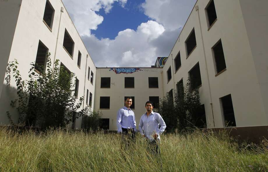 Gaurav Khandelwal, left, and Apurva Sanghavi, right, stand in front of the former Schlumberger building at the corner or Leeland and Delano Streets. The two plan to redevelop the building in the East End. Photo: Cody Duty, Houston Chronicle