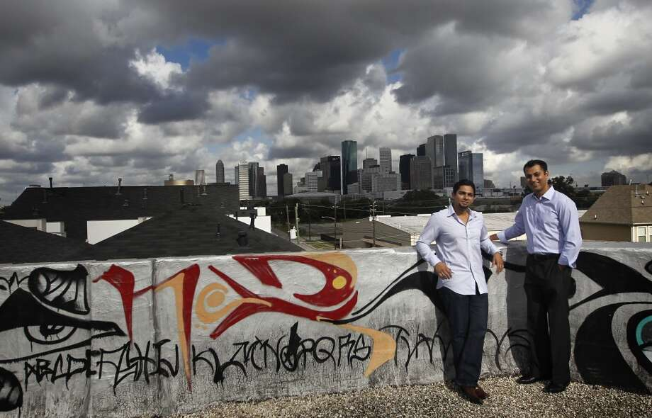 Apurva Sanghavi, left, stands with Gaurav Khandelwal, right, on the top of the former Schlumberger building at the corner or Leeland and Delano Streets. The two plan to redevelop the building in the East End. Photo: Cody Duty, Houston Chronicle
