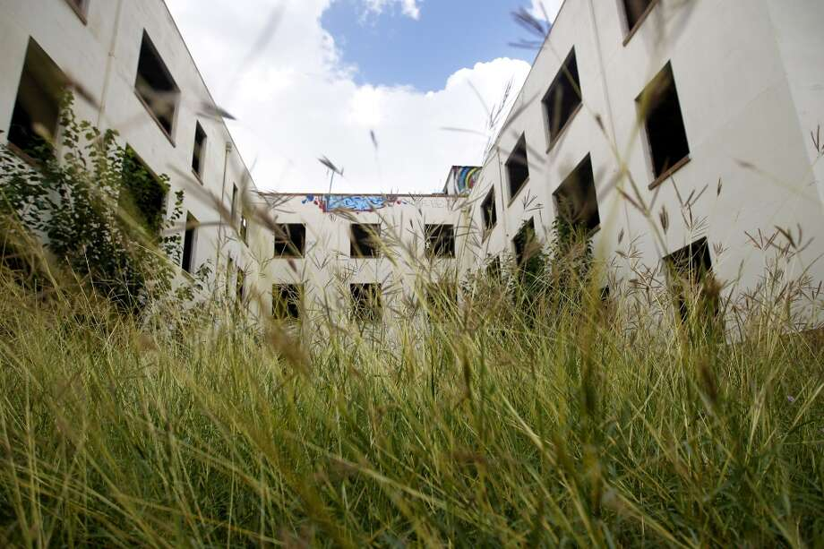Tall grass grows around the former Schlumberger building at the corner or Leeland and Delano Streets. Gaurav Khandelwal and Apurva Sanghavi plan to redevelop the building in the East End. Photo: Cody Duty, Houston Chronicle
