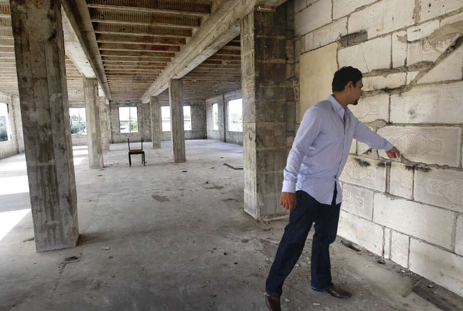 Apurva Sanghavi touches an original portion of the former Schlumberger building at the corner or Leeland and Delano Streets. Gaurav Khandelwal and Apurva Sanghavi plan to redevelop the building in the East End. Photo: Cody Duty, Houston Chronicle