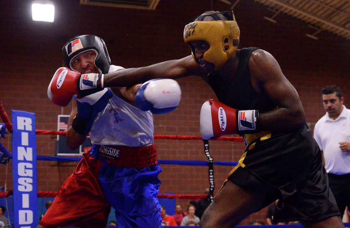 Antonio Tessatore from the Howard Street Boxing Club, left, fights Robel Biru from the Bumble Bee Boxing Club during the 4th annual Central District Boxing Revival Saturday, Oct. 5, 2013 at the Garfield Community Center in Seattle. Boxers from all over the Northwest region, ranging from ages 8-34, competed in Saturday's event.
