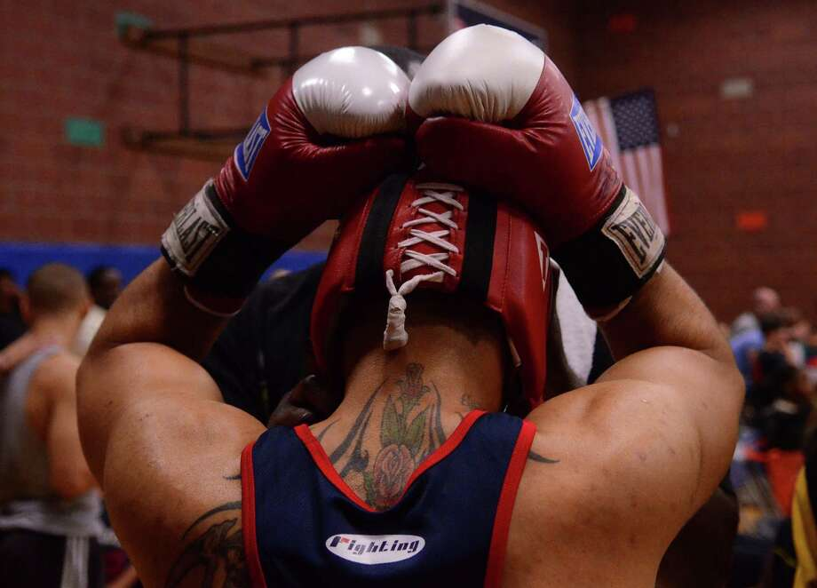 A fighter has his helmet fitted during the 4th annual Central District Boxing Revival Saturday, Oct. 5, 2013 at the Garfield Community Center in Seattle. Boxers from all over the Northwest region, ranging from ages 8-34, competed in Saturday's event. Photo: SY BEAN, SEATTLEPI.COM / SEATTLEPI.COM