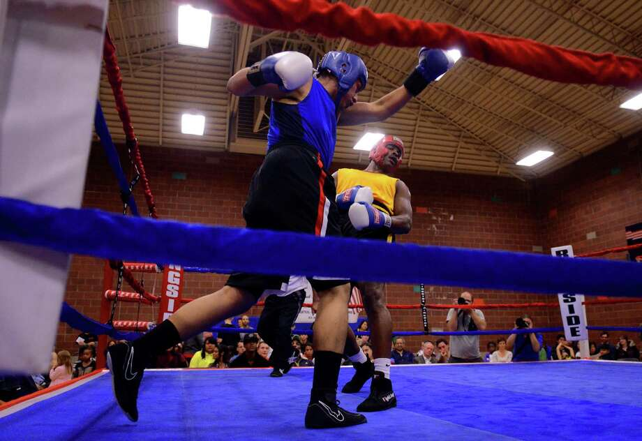 Alonso Rios from the Squared Circle Boxing Club misses a left hook against his opponent, Michael Powel from the Wildcat's Boxing Club, during the 4th annual Central District Boxing Revival Saturday, Oct. 5, 2013 at the Garfield Community Center in Seattle. Boxers from all over the Northwest region, ranging from ages 8-34, competed in Saturday's event. Photo: SY BEAN, SEATTLEPI.COM / SEATTLEPI.COM