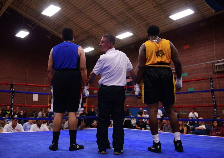 The referee looks to the judges for the decision after Michael Powell and Alonso Rios fought in the 201+ weight class during the 4th annual Central District Boxing Revival Saturday, Oct. 5, 2013, at the Garfield Community Center in Seattle. Photo: SY BEAN, SEATTLEPI.COM / SEATTLEPI.COM