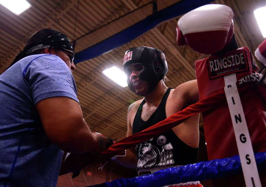 Jorge Vila from the Nation of Outlawz Boxing Club removes his gloves after fighting Calvin Taylor from the Wildcat's Boxing Club during the 4th annual Central District Boxing Revival Saturday, Oct. 5, 2013 at the Garfield Community Center in Seattle. Boxers from all over the Northwest region, ranging from ages 8-34, competed in Saturday's event. Photo: SY BEAN, SEATTLEPI.COM / SEATTLEPI.COM