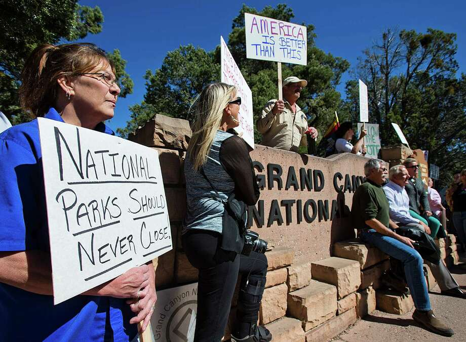 Nearly 100 protesters  gather  outside the south entrance to the Grand Canyon to complain about  the federal government's refusal to accept financial assistance from local business owners to reopen the park. The shutdown is hurting the nation. Photo: Tom Tingle, Associated Press / The Arizona Republic