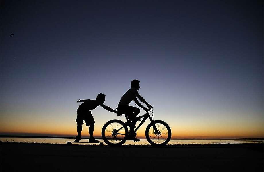 Pull session:Kyle Queyrouze catches a ride on his friend Nicolas Knauf's bike in Mandeville, La. Photo: David Grunfeld, Associated Press