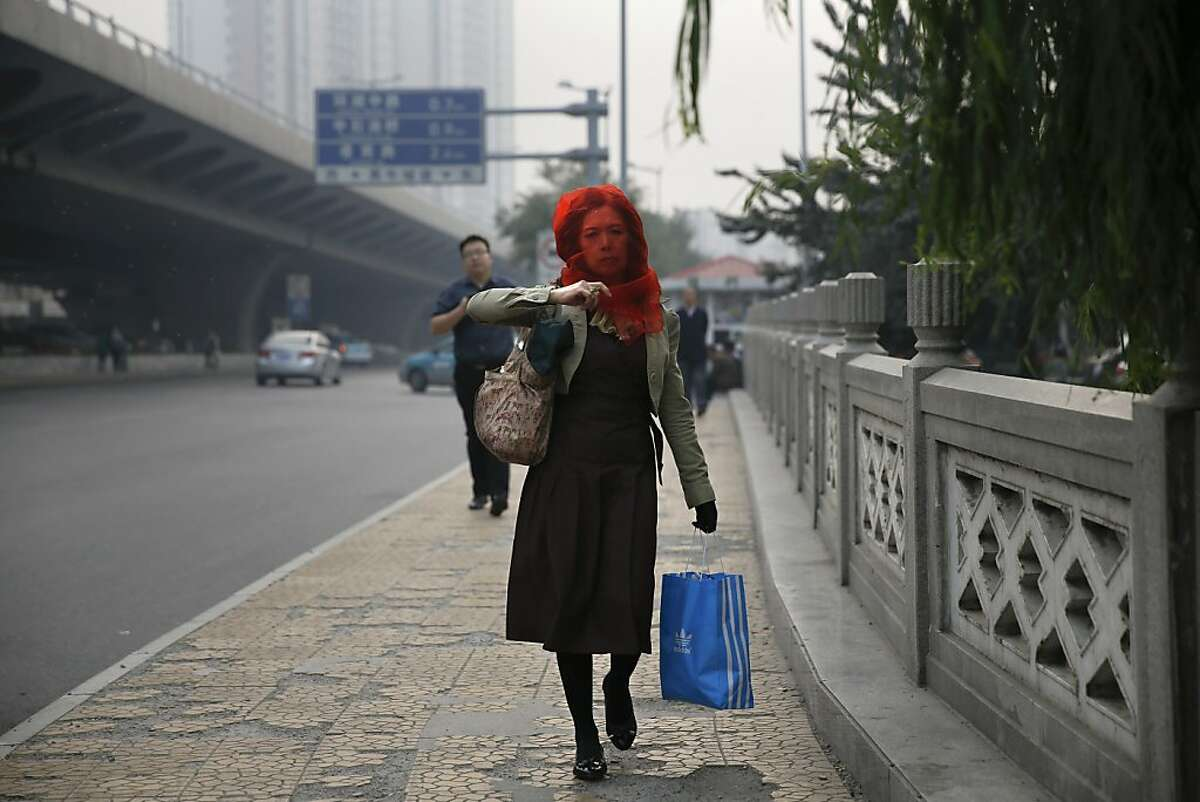 The lady in red: A woman adjusts her scarf as she strolls down the street on a smoggy day in Tianjin, China.