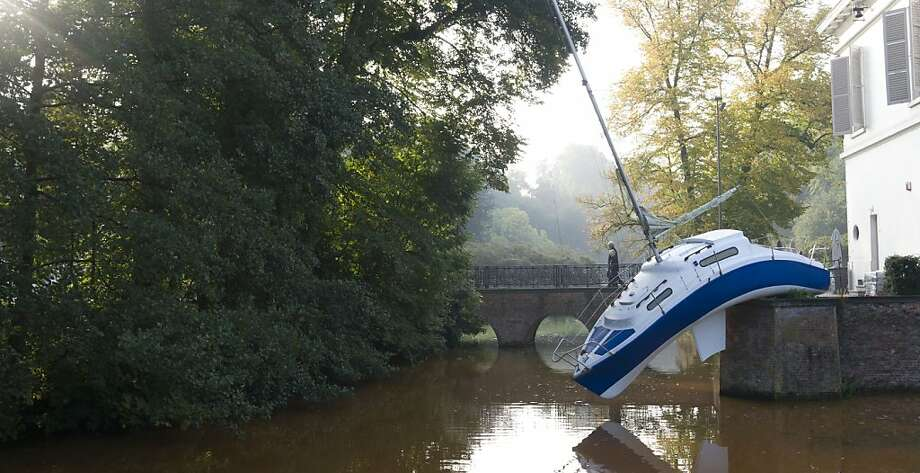 "The water's a little low this time of year: Double takes often occur on the bridge behind Austrian artist Erwin Wurm's installation ""Misconceivable"" in Wilrijk, Belgium. Photo: Virginia Mayo, Associated Press"