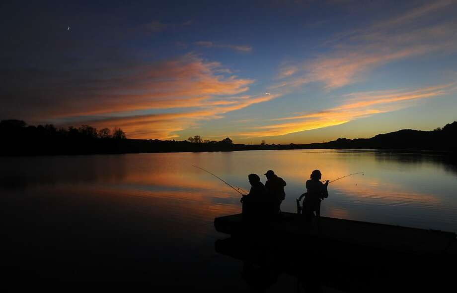 Three friends try their luck fishing on the floating dock at Briar Creek Lake near Berwick. Pa. Photo: Jimmy May, Associated Press