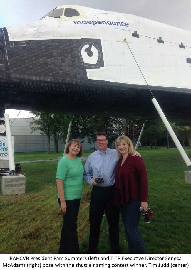 Pam Summers (left), president of Bay Area Houston Convention and Visitors Bureau, and TITR executive director Seneca McAdams (right) pose with the shuttle naming contest winner, Tim Judd. Photo: Photo Provided