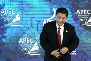 Xi Jinping, China's president, arrives for a session during the Asia-Pacific Economic Cooperation (APEC) CEO Summit in Nusa Dua, Bali, Indonesia, on Monday, Oct. 7, 2013. Asia-Pacific governments are calling for vigilance against protectionism as economic growth slows in parts of the region and completion of a 12-nation trade accord looks set to be delayed further. Photographer: SeongJoon Cho/Bloomberg *** Local Caption *** Xi Jinping