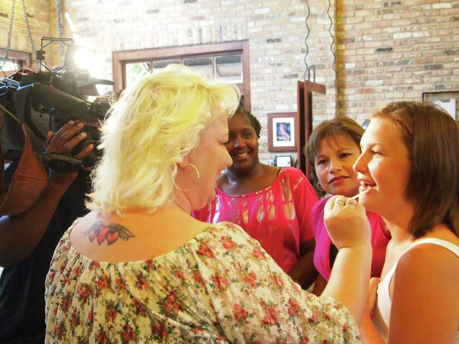 Tonia Cloninger, a grandmother, mother and survivor, helps Elizabeth Stokes (far right), who found her cancer when she was 21, with a few tips at a makeover event provided for patients of The Rose and other breast health care organizations.