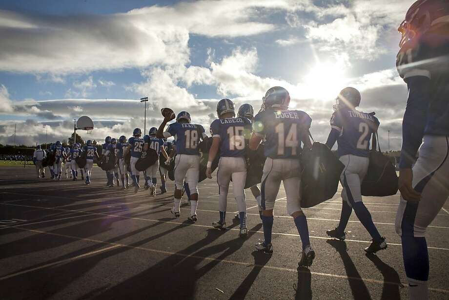 Junipero Serra high school's football team, the Padres, walks out onto the field before a game at Encinal  high school against the Jets in Alameda on September 21st 2013. Photo: Sam Wolson, Special To The Chronicle