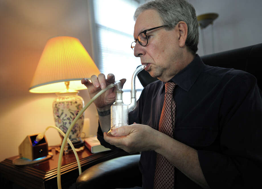 """Robert Specht uses a vaporizer to medicate with medical marijuana at his home in Hamden, Conn. on Wednesday, October 9, 2013. Specht suffers from severe, chronic pain resulting from injuries and surgeries to his foot, knee, and hip. """"Cannibis doesn't eliminate my pain,"""" Specht says. """"It distracts me from it."""" Photo: Brian A. Pounds / Connecticut Post"""