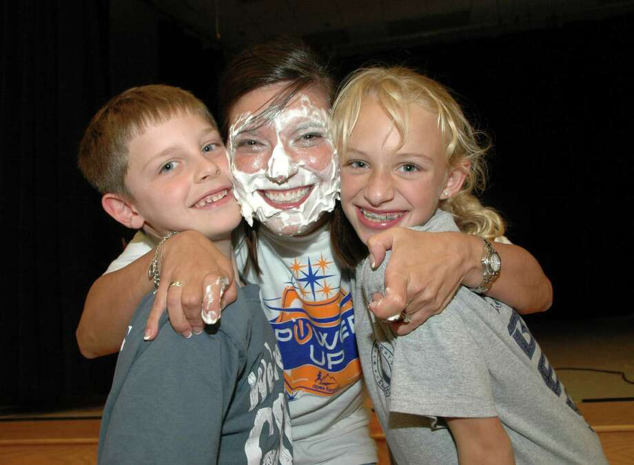 Principal Heather Moore smiles with Ty Doucet and Sadie Lewis after the students each gave her a pie to the face. It was part of the monthly Rahe Rahe Rally, and a reward for students reaching a set number of laps and fundraising goal during the Apex Fun Run in September. Photo: Courtesy Photo