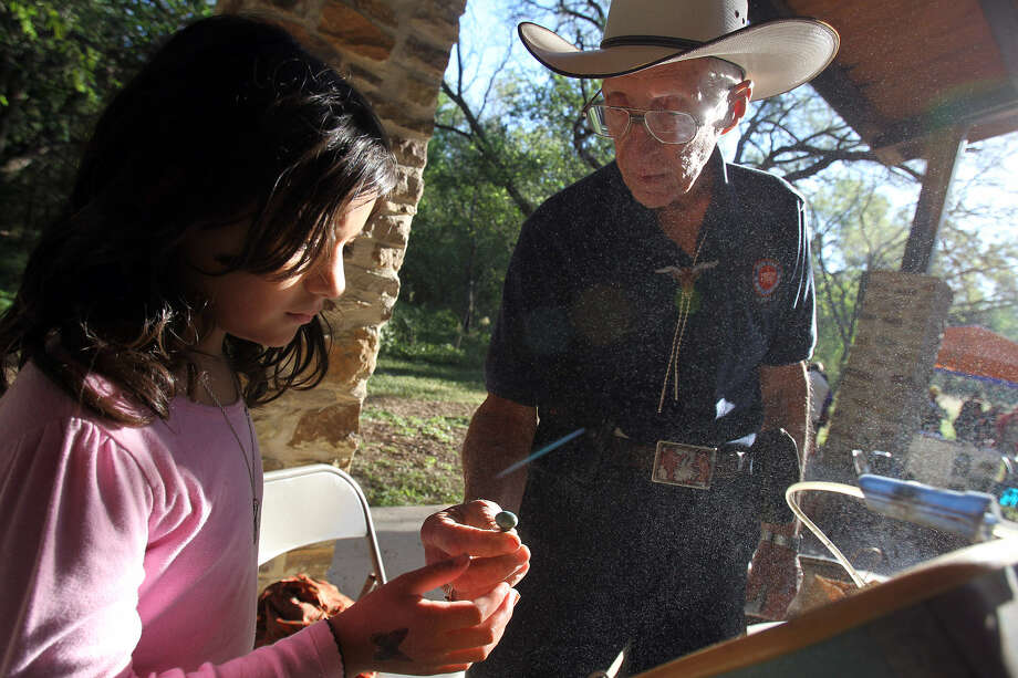 A girl looks at the piece of turquoise she has polished during the annual Fall Fest at Medina River Natural Area a few years ago. Photo: JENNIFER WHITNEY / Special To The Express-News