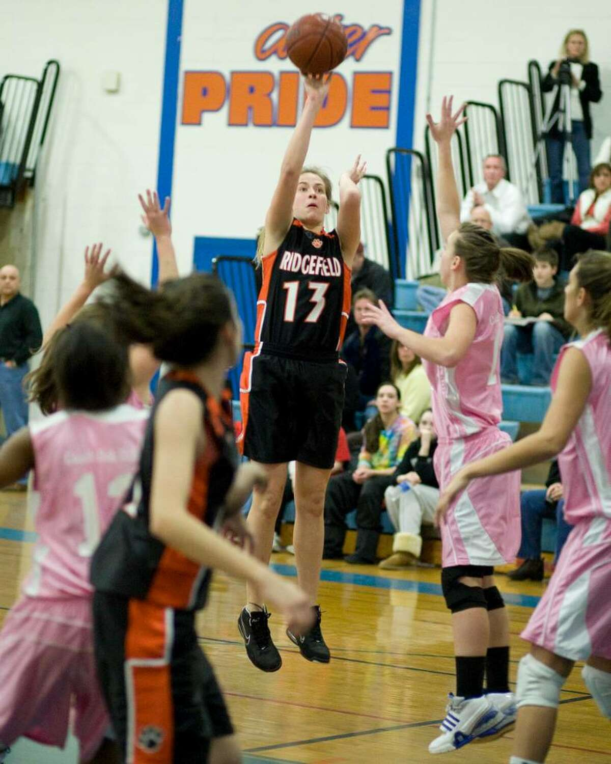 Ridgefield's Michelle Gibbons (13) pops a jump shot over Danbury defender Nicole Kline during their FCIAC game Tuesday night at Danbury High.