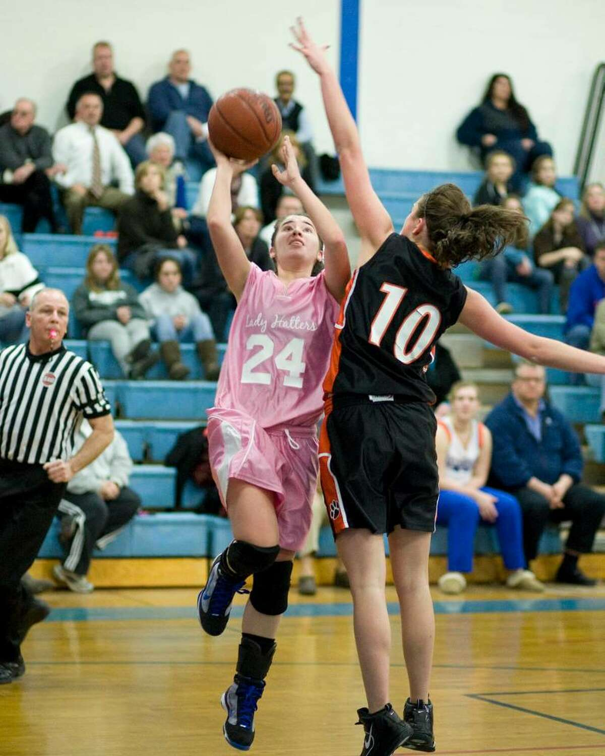 Danbury's Allison Kornhaas (24) drives to the basket while Ridgefield defender Kathryn Cholko goes for the block during their FCIAC game Tuesday night at Danbury High.