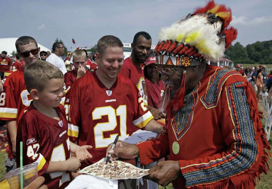 "Zena ""Chief Z"" Williams, unofficial mascot of the Washington Redskins, signs autographs during fan appreciation day. The name Washington Redskins has inspired protests, hearings, editorials, lawsuits, letters from Congress, even a presidential nudge. Photo: Alex Brandon / Associated Press"