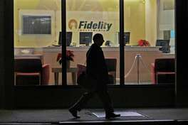 FILE - In this Thursday, Dec. 4, 2008 file photo, a man walks past a Fidelity Investments office in the Financial District of downtown Boston. On Wednesday, Oct. 9, 2013, the nation's largest manager of money market mutual funds said that it no longer holds any U.S. government debt that comes due around the time the nation could hit its borrowing limit. Money market portfolio managers at Fidelity Investments have been selling off their government debt holdings over the last couple of weeks, said Nancy Prior, president of Fidelity's Money Market Group. While Fidelity expects the debt ceiling issue to be resolved, the Boston-based asset manager said it is taking steps to protect investors. (AP Photo/Charles Krupa)