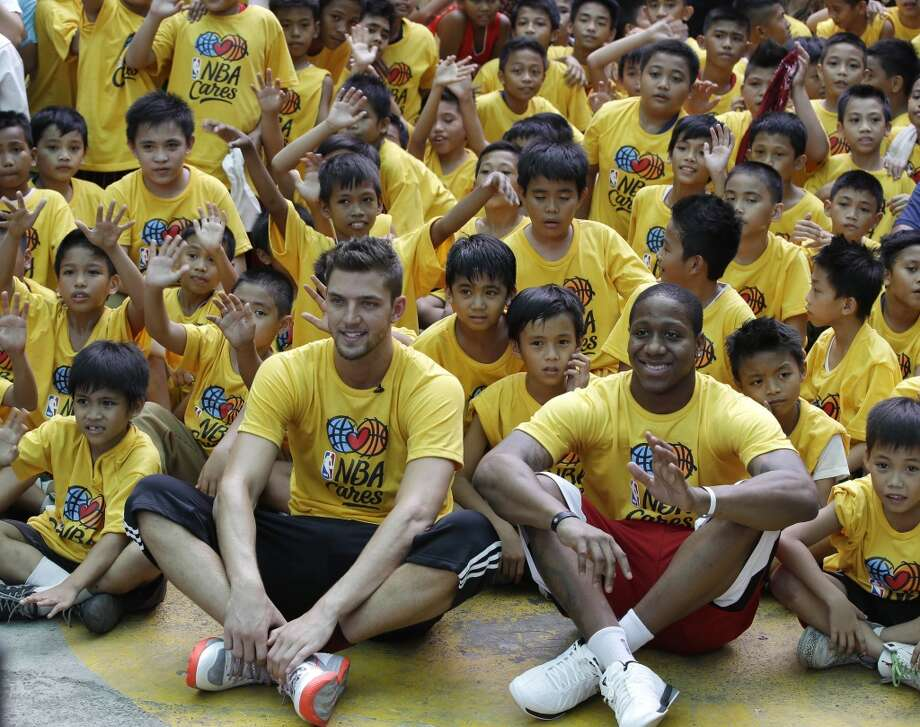 Isaiah Canaan and Chandler Parsons of the Rockets interact with young basketball fans in the Philippines. Photo: Bullit Marquez, Associated Press