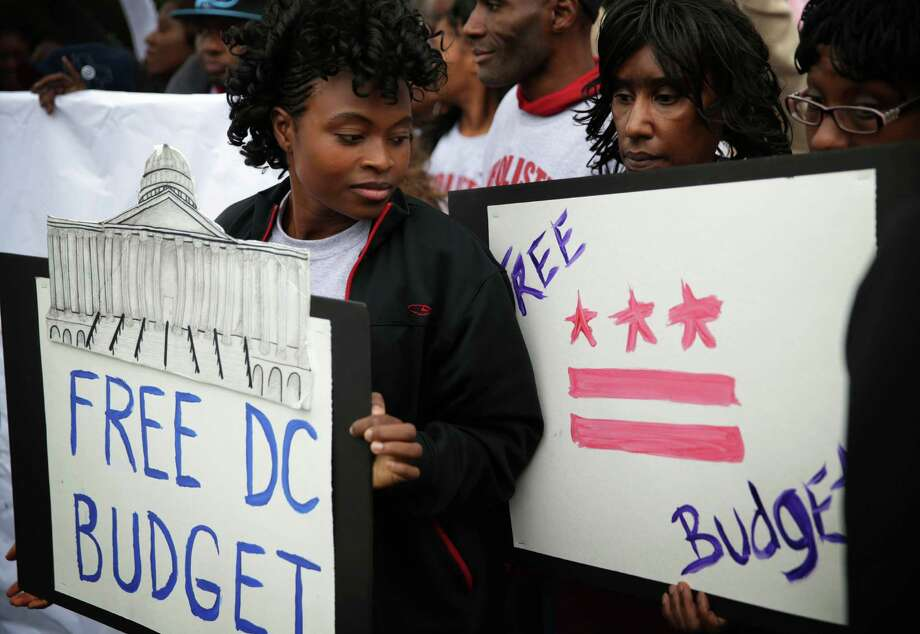"""WASHINGTON, DC - OCTOBER 09:  Local residents hold signs during a news conference with members of the Washington, DC Council """"to call on the Senate and the administration to free DC's local budget during the federal government shutdown"""" at the Senate Swamp October 9, 2013 on Capitol Hill in Washington, DC. On the ninth day of a government shutdown, Senate Democrats said they will negotiate with the Republicans after the government reopens.  (Photo by Alex Wong/Getty Images) ORG XMIT: 183922150 Photo: Alex Wong / 2013 Getty Images"""