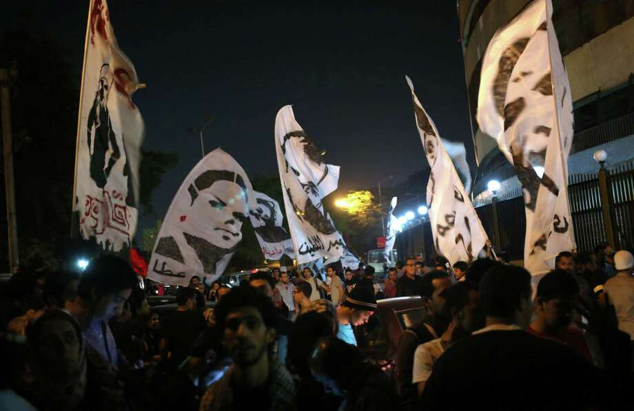 Egyptian protesters wave white banners with portraits of some of 26 people killed in 2011 as they mark the second anniversary of a military crackdown on protesters outside Egypt's state TV building in Cairo, Egypt, Wednesday, Oct. 9, 2013. Hundreds of Egyptians held candles, waved pictures of slain protesters and demanded retribution from former generals while marking the second anniversary of the killing of 26 people, mostly Christians, in the military crackdown outside the state TV building. (AP Photo/Khalil Hamra) ORG XMIT: KH102 Photo: Khalil Hamra / AP
