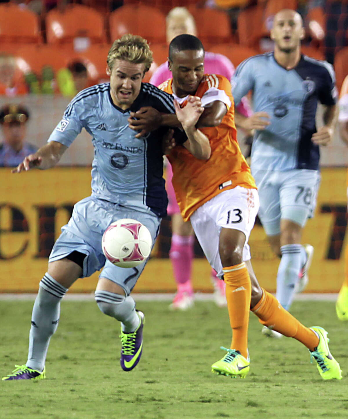 Sporting KC defender/midfielder Chance Myers left, and Houston Dynamo midfielder Ricardo Clark right, tangle during the first half of MLS game action at BBVA Compass Stadium Wednesday, Oct. 9, 2013, in Houston.