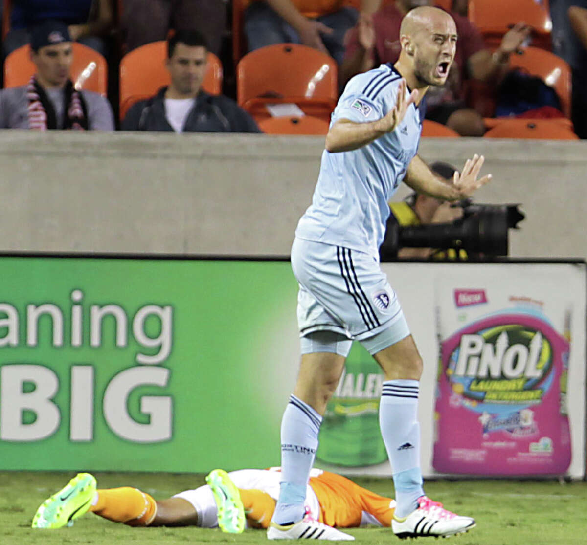 Sporting KC defender Aurelien Collin right, reacts after receiving a yellow card as the Houston Dynamo midfielder Ricardo Clark left, lies on the field during the first half of MLS game action at BBVA Compass Stadium Wednesday, Oct. 9, 2013, in Houston.