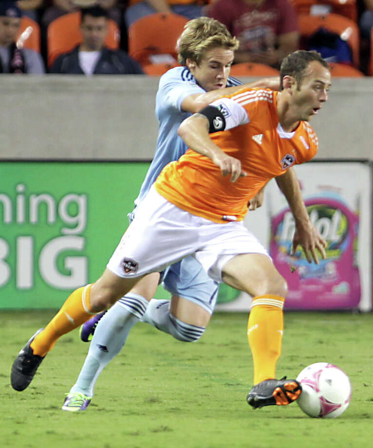 Sporting KC defender/midfielder Chance Myers left, holds on to Houston Dynamo midfielder Brad Davis right, during the first half of MLS game action at BBVA Compass Stadium Wednesday, Oct. 9, 2013, in Houston. Photo: James Nielsen, Houston Chronicle / © 2013  Houston Chronicle