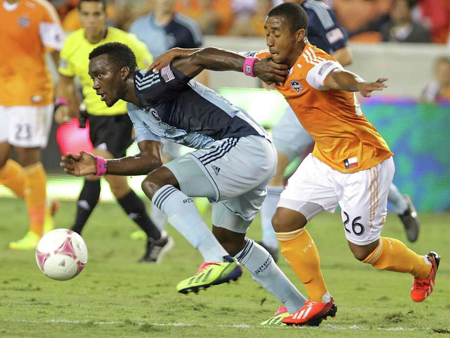 Sporting KC forward C.J. Sapong left, and Houston Dynamo midfielder Corey Ashe right, during the first half of MLS game action at BBVA Compass Stadium Wednesday, Oct. 9, 2013, in Houston. Photo: James Nielsen, Houston Chronicle / © 2013  Houston Chronicle