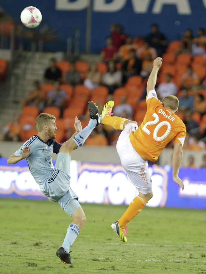 Sporting KC midfielder Oriol Rosell left, and Houston Dynamo midfielder Andrew Driver right, during the first half of MLS game action at BBVA Compass Stadium Wednesday, Oct. 9, 2013, in Houston. Photo: James Nielsen, Houston Chronicle / © 2013  Houston Chronicle