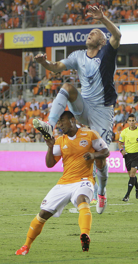 Sporting KC defender Aurelien Collin top, and Houston Dynamo midfielder Corey Ashe bottom, during the first half of MLS game action at BBVA Compass Stadium Wednesday, Oct. 9, 2013, in Houston. Photo: James Nielsen, Houston Chronicle / © 2013  Houston Chronicle