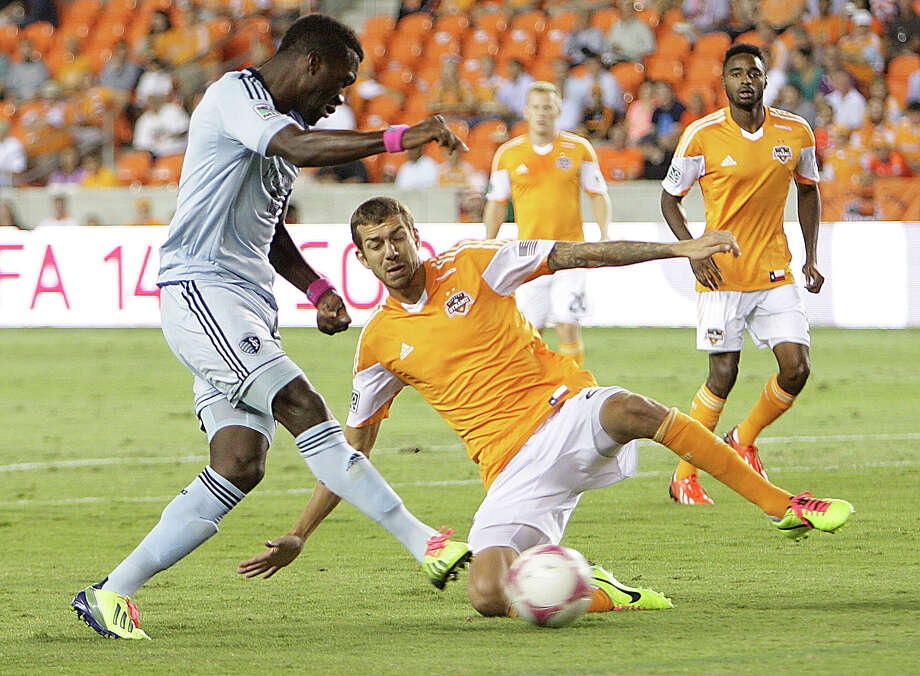 Sporting KC forward C.J. Sapong left, and the Houston Dynamo defender Eric Brunner during the first half of MLS game action at BBVA Compass Stadium Wednesday, Oct. 9, 2013, in Houston. Photo: James Nielsen, Houston Chronicle / © 2013  Houston Chronicle