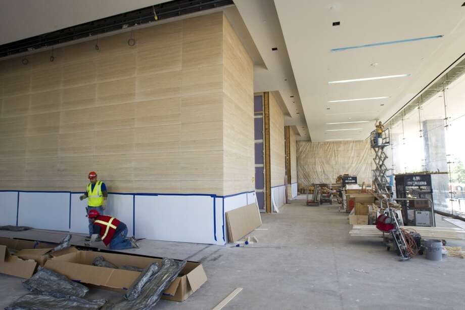 Workers continue construction of the walls and ceiling of the Hackett Tower's main lobby on Oct. 9, 2013, in The Woodlands. Photo: Brett Coomer, Houston Chronicle