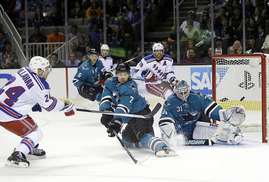 The Sharks' Brad Stuart (center) defends against the Rangers' Ryan Callahan in the second period Tuesday. Photo: Marcio Jose Sanchez, Associated Press