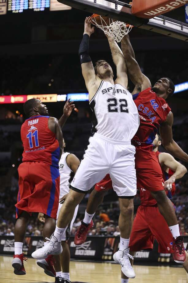 San Antonio Spurs' Tiago Splitter splits the defense of CSKA Moscow Jeremy Pargo, left, and Kyle Hines during a dunk in the second half of an exhibition game at the AT&T Center on Wednesday, Oct. 9, 2013. The Spurs won in overtime 95-93. Photo: Jerry Lara, San Antonio Express-News
