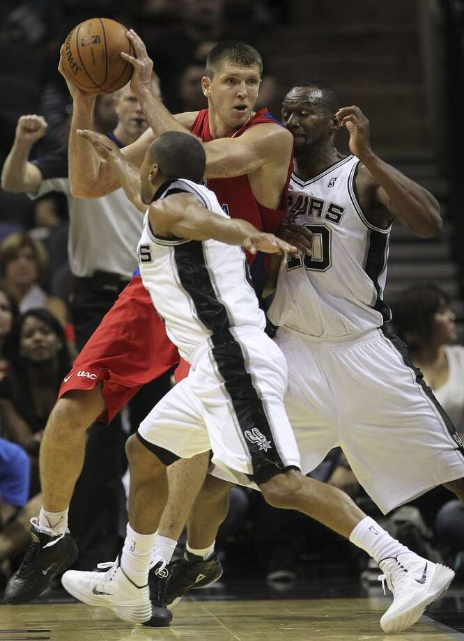 San Antonio Spurs' Patty Mills, front, and Sam Young put pressure on CSKA Moscow Viktor Khryapa during the second half of an exhibition game at the AT&T Center on Wednesday, Oct. 9, 2013. The Spurs won in overtime 95-93. Photo: Jerry Lara, San Antonio Express-News