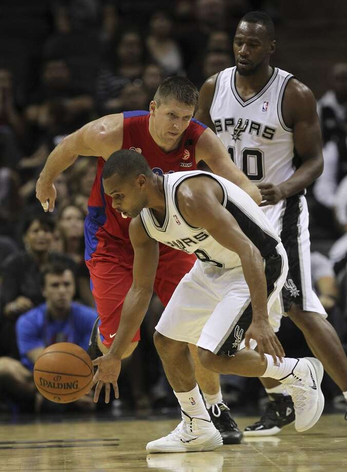 San Antonio Spurs' Patty Mills picks up a loose ball as CSKA Moscow Viktor Khryapa tries to catch up during the second half of an exhibition game at the AT&T Center on Wednesday, Oct. 9, 2013. The Spurs won in overtime 95-93. In back is Sam Young. Photo: Jerry Lara, San Antonio Express-News