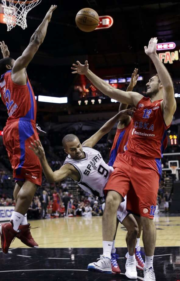 San Antonio Spurs' Tony Parker (9), of France, is fouled by CSKA Moscow's Nedad Krstic (12) as he drives to the basket during the first half of an exhibition NBA basketball game, Wednesday, Oct. 9, 2013, in San Antonio. CSKA Moscow's Kyle Hines, left, also defends on the play. Photo: Eric Gay, Associated Press