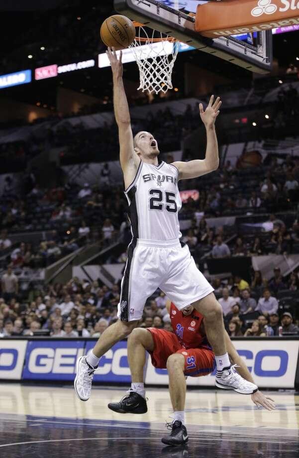 San Antonio Spurs' Nando De Colo (25), of France, scores over CSKA Moscow's Victor Khryapa (31) during the second half of an exhibition NBA basketball game, Oct. 9, 2013, in San Antonio. San Antonio won 95-93 in overtime. Photo: Eric Gay, Associated Press