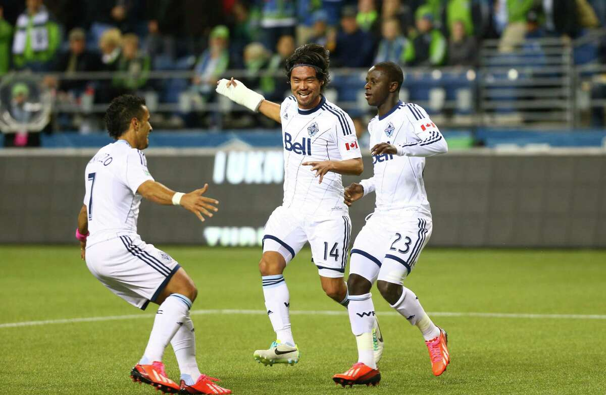 Vancouver Whitecaps players, from left, Camilo Sanvezzo, Daigo Kobayashi and Kekuta Manneh celebrate a goal by Manneh in the first half of a match Wednesday, October 9, 2013 at CenturyLink Field in Seattle.