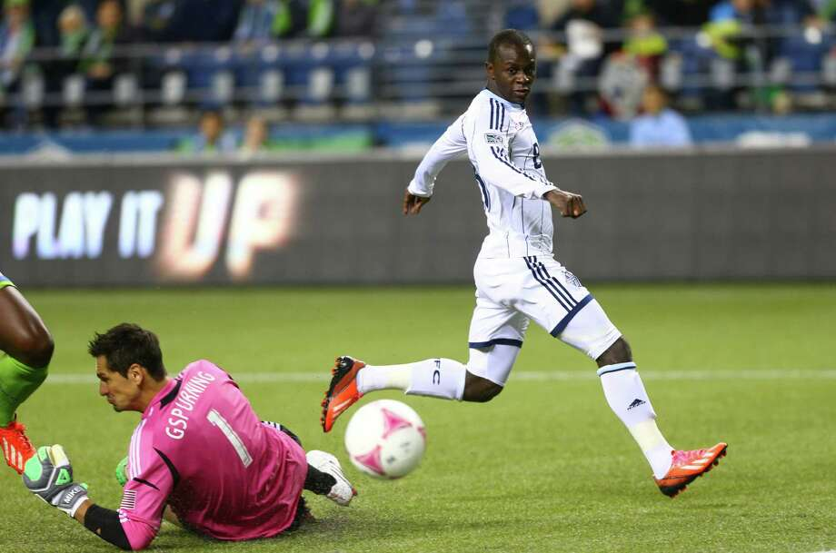 Vancouver Whitecaps player Kekuta Manneh gets the ball around Seattle Sounders goalie Michael Gspurning for a goal in the first half of a match Wednesday, October 9, 2013 at CenturyLink Field in Seattle. Photo: JOSHUA TRUJILLO, SEATTLEPI.COM / SEATTLEPI.COM