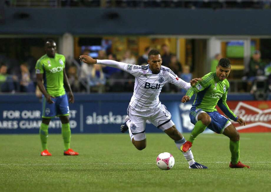 Vancouver Whitecaps midfielder Matt Watson and Seattle Sounders defender DeAndre Yedlin race for the ball during the Seattle Sounders vs. Vancouver Whitecaps game at Centurylink Field on Wednesday, Oct. 8, 2013. Photo: SOFIA JARAMILLO, SOFIA JARAMILLO/SEATTLEPI.COM / SEATTLEPI.COM