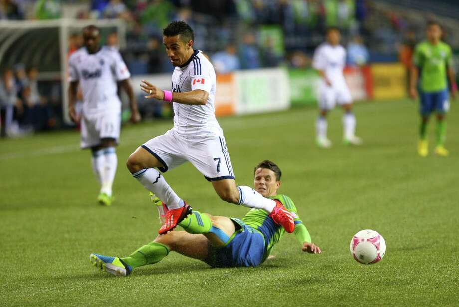 Vancouver Whitecaps player Camilo Sanvezzo gets tangled with Seattle Sounders player Marc Burch in the first half of a match Wednesday, October 9, 2013 at CenturyLink Field in Seattle. Photo: JOSHUA TRUJILLO, SEATTLEPI.COM / SEATTLEPI.COM