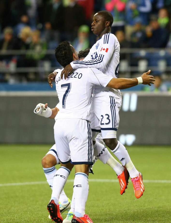 Vancouver Whitecaps players Daigo Kobayashi and Kekuta Manneh celebrate a goal by Manneh in the first half of a match Wednesday, October 9, 2013 at CenturyLink Field in Seattle. Photo: JOSHUA TRUJILLO, SEATTLEPI.COM / SEATTLEPI.COM